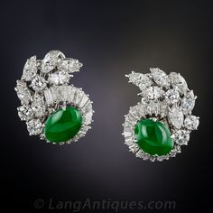 A matched pair of gorgeous green oval jades are augmented with resplendent platinum and diamonds in these magnificent, high-quality, platinum and diamond earrings, circa mid-twentieth century. The strikingly colorful gemstones are embraced by mirror-like swirls of closely set tapered baguette diamonds leading to sparkling cascades of bright-white round and marquise diamonds, for a total diamond weight of 5.25 carats. The jades are accompanied by an American Gemological Laboratory (AGL)…