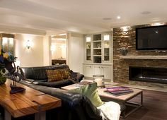 basement idea....LOVE the stone wall behind the tv and shelving surrounding...