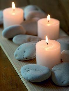 Para um arranjo minimalista e elegante, misture velas e pedras sobre uma tábua de madeira