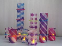 Colorful candle wraps made out of dollar store plastic folders! This would be super easy and it might even look better with tape/glue instead of the bracelets…
