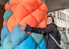 Psychology major Tatiana Kvetnaya hugs artist Cameron Kelly's playful sculpture, which emits soothing sounds and lights up when squeezed. The public art project was hosted by the University Art Gallery.