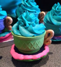 "Teacup cupcake. Entirely edible. Cake batter baked in an ice cream cone, then trimmed off and sat on a sugar cookie. Both the cookie and the cone were then covered with royal icing and a fondant handle was attacked with modeling chocolate ""glue"". Topped with buttercream."