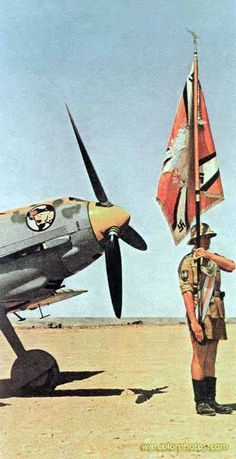 A German Afrikakorps Luftwaffe soldier takes part in a military exercise whilst wielding the Luftwaffe battle flag. The soldier pictured was a member of the Bf 109 E-4/Tropical Fighters division, unit I/JG 27 stationed in North Africa.