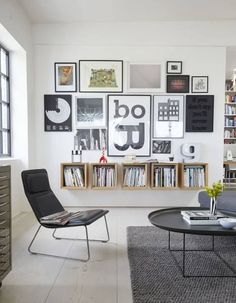 This is perfect for a large, empty wall. Frames arranged close to each other with square boxes underneath.