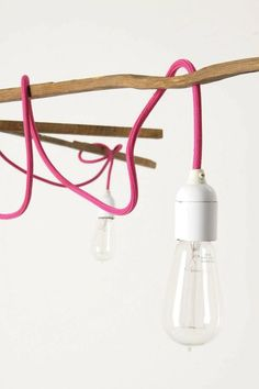 A pink fabric cord winds around the frame, showcasing three bare bulbs. The Tobacco Stick Chandelier is $1,298 at Anthropologie.