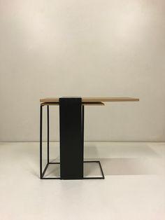 """Ancre est une ligne de table basse en acier laminé à chaud et chêne. Elle s'inspire des façades des bâtiments du Bauhaus et de leurs porte-à-faux. La structure en acier, par son positionnement, permet de maintenir le plateau de bois. """"Cette esthétique découle d'une recherche autour de la maison de poupée. Et si son architecture évoluait vers le modernisme ? Au fil des dessins, la maison est devenue table"""" explique Thomas Dumoulin, ébéniste designer."""