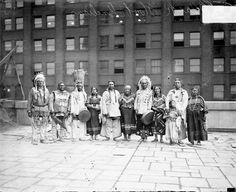 Informal full-length group portrait of a group of men, women, and a child, members of the Blackfoot Indian tribe, wearing traditional Native American clothing, standing in a row on the roof of a building in Chicago, Illinois. 1929