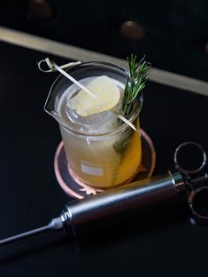 The Peaty Penicillin Cocktail, dark back with syringe and garnish Penicillin Cocktail, Alcoholic Drinks, Cocktails, Long Hours, Long Weekend, Happy Hour, The Cure, Magazine, Meals