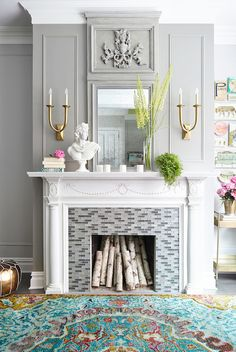 Fabulous living room features traditional fireplace mantel accented with linear glass glass mosaic tile surround illuminated by Studio French Deco Horn Double Sconce flanking a gray mirror.