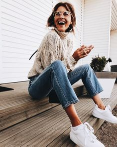 Cozy beige cable knit sweater with blue jeans.