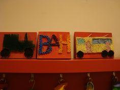 Een naambordje (initialen van vader, moeder en achternaam) in spijkers weergegeven. Groep 5/6 OBS Woold