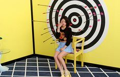 EunB doing the Illuminati One-Eye sign while arrows are shot at her.