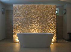 Badezimmer mit Badewanne und Rückwand aus Stein
