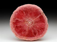 A pleasing richly coloured pink polished slice of the classic rhodochrosite stalactite from the Capillitas Mine, Argentina.  Crystal Classics Minerals