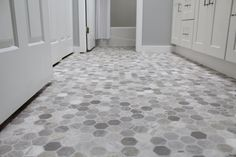 Vinyl flooring with a gray hexagon pattern looks just like expensive tile. It is a low-cost low-maintenance alternative to spending a fortune on your bathroom floor.