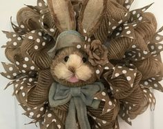 This large natural colored poly burlap deco mesh Easter wreath will spice up any door/room this holiday season.  The wreath is made of poly burlap deco mesh. It is accented throughout with polka dot ribbon. The natural sisal grass bunny is accented with orange burlap floppy hat accented with a burlap and lace shabby chic handmade flowers with pearls in the center and a orange burlap bow with a pearl accented flower around her neck. This wreath measures approximately 24 inches Ready for i...
