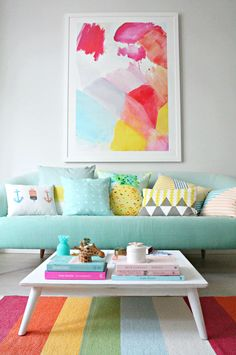 What a gorgeous, colourful sitting room. Rainbow rug, watercolour art print, a light blue sofa and comfy bright pillows.