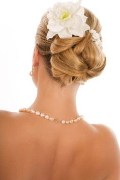 Here is a pretty bridal updo with flowers. This bride has used a large white flower along with some baby's breath to decorate the back portion of this traditional hairdo that would work nicely with medium to long length straight hair. Ideas for updos is helpful for those who are planning weddings or other formal events.-pin it by #carden