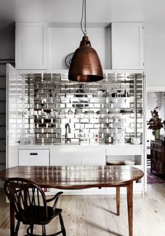 Shiny mirrored tile backsplash in a kitchen by Emma Templeton