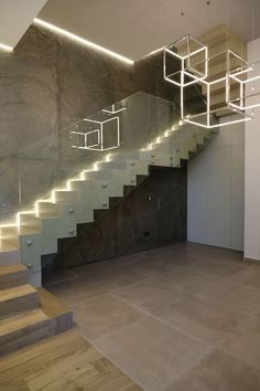 Escalera de acceso a vivienda. Losa de hormigón peldañeada revestida en porcelánico imitación cemento y madera. Barandilla en cristal templado. Revestimiento de pared en pizarra laminada. Iluminación indirecta mediante led. Diseño realizado y coordinado por AZ diseño.