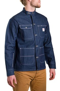LOT-1745c The Indigo Denim Chore Coat with Banded Collar is made of lightweight 100% cotton and is machine washable. This coat has 4 top-loading patch pockets, one of which snaps. It polished nickel b
