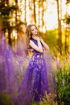 Скачать - Девушка с цветами Люпин в поле на закате — стоковое изображение #103270176