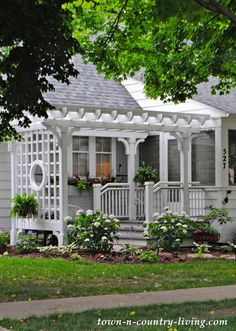 "White front porch w/ pergola & trellis (round ""window"") on older home in Geneva, Illinois"