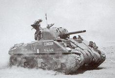 Un Sherman M4 britannique sur un sol poussiéreux, à proximité de Paterne