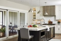 A set of new sliding doors created a seamless visual transition between the kitchen and screen porch, allowing endless natural light to fill the space. Quartz Kitchen Countertops, Granite Kitchen, Dining Table Chairs, Dining Room, White Herringbone Tile, Curved Kitchen Island, Beach Kitchens, White Kitchens, Built In Buffet