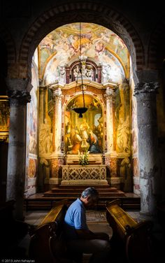 A man sits quietly in the Triesle Cathedral (Cattedral di San Giusto) near San Giosto castle, Triesle, Italy