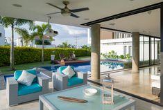 La terraza cubierta es un espacio fresco y protegido del sol, amueblado de manera confortable. Las sillas y la mesa de centro son de ratán blanco y están decoradas con cojines azules de Turquesa.