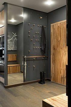 Décorer un couloir. Un mur gris et un miroir. Une paire de bottes noires.