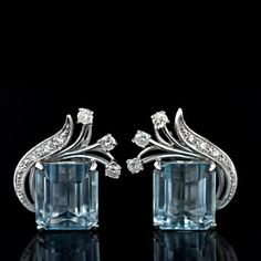 1950s Aquamarine ear clips. A matched pair of pastel blue emerald cut aquamarines are enhanced with a sweeping diamond spray. A classic vintage look rendered in 14 karat white gold. [via http://helenmckees.tumblr.com]