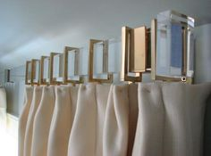 Lucite curtain rod with rectangular brass rings.
