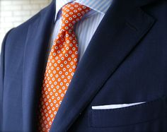 Navy jacket, white shirt with light blue candy stripes, orange tie with white and blue polka dots