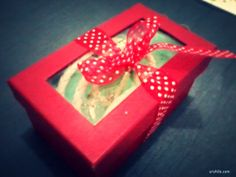 Recycled rectangular gift box. Use of embroidered fabric and polka-dot ribbon to adorn.