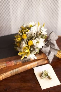 A beautiful bouquet of yellow and white flowers, tied with a muted pearl gray ribbon.