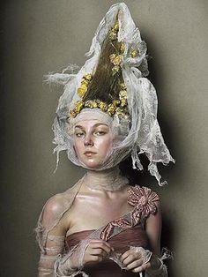 No editorial Couture para a Vogue, Steven Meisel fotografou a modelo a usar um toucado e um penteado com uma verticalidade acentuada e um ligeiro gorjal a envolver o pescoço, que lembram um hennin.
