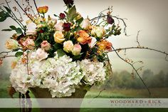 Large floral arrangement with hydrangea, orange, red, pink and white roses  Woodward + Rick photography