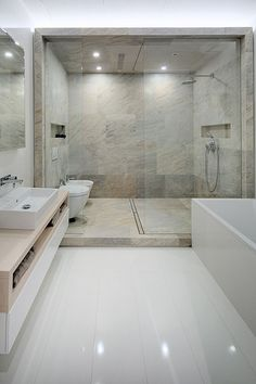 12 Design Ideas For Including Built-In Shelving In Your Shower // The stone shower and toilet area in this bathtub area both have built in shelving.