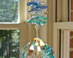 Este encantador suncatcher fue creado usando giro cristal del diamante de Swarovski 2 pulgadas (50x31mm). Facetas del remolino alrededor del prisma, produciendo bellos arco iris en la luz del sol. El colgante es Strass logo grabado al agua fuerte. El filamento de la 6¼ consiste en abalorios de cristal de Swarovski claro acentuados con rosa perlas de Swarovski, perlas de Swarovski y un cubo de cristal de Swarovski rosa en el centro. La longitud entera, incluyendo el 1¼ lazo de suspensión, es…