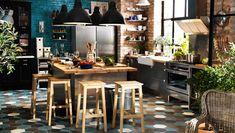 Une déco de grande cuisine qui mixe meubles noirs et inox, ilôt central inox plateau bois clair grandes suspensions noires et un carrelage s...