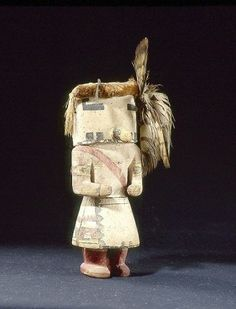 coll. BRETON, poupée kachina représente un personnage portant un masque coiffé d'une frange de fibres rases, un plumet rattaché sur le côté gauche du visage. Les bras sont décorés de motifs en escalier symbolisant des nuages.