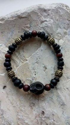 Armband gemaakt van zwarte en bruine houten kralen, oud goude kralen en een doodskop.