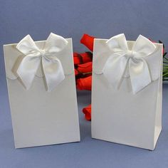 """Each box measures 5 ¾"""" tall x 3 ½"""" wide with a white iridescent finish for a beautiful sheen and a distinctive fluted front flap top and matching white bow that can be secured with an included self sticking strip."""