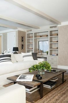 Under a ceiling accented with dove gray wood beams is positioned over an ivory linen sectional topped with black and white pillows and placed on a jute rug facing a wood and iron coffee table.