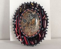This beautiful brooch has a focal cabochon set on black shibori silk with pink and orange streaks. It has been created with careful attention