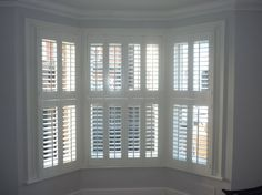 Bay window in St Albans with white wooden tier on tier shutters.