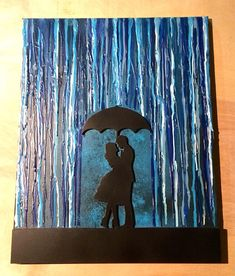 This melted crayon art painting is of a couple standing together under an umbrella in the rain.  The painting was done on a 16x20 canvas. To create it, various shades of blue crayon was melted onto the canvas, which was prepped using various shades of acrylic paint. The silhouette of