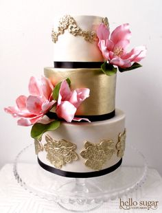 Gold, black & pink wedding cake with green leaf accents.